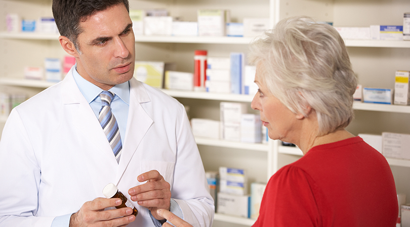 American pharmacist with senior woman in pharmacy discussing medication