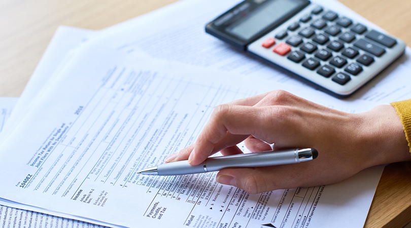 woman reviewing document with calculator and pen